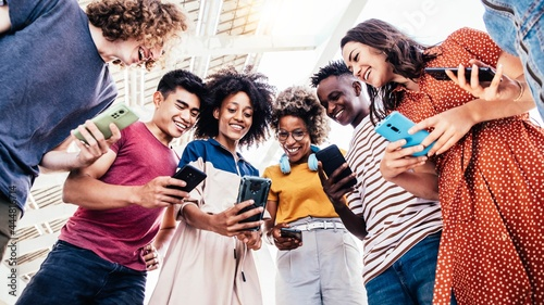 Canvas Diverse teenage students using digital smart mobile phones on college campus - G