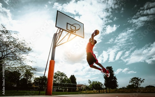 Fotografering Street basketball player making a powerful slam dunk on the court - Athletic mal