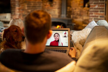 Man With Dog Video Conferencing With Colleagues On Living Room Sofa