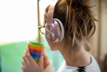 Woman With Coffee Listening To Music On Headphones