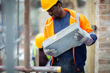 Construction Worker Carrying Brick At Construction Site