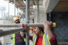 Female Construction Worker Assembling Scaffolding