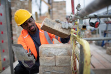 Male Construction Worker Laying Bricks At Construction Site