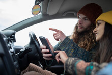 Young Couple With Smart Phone On Road Trip In Car