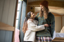 Happy Young Couple Hugging In Tiny Cabin Rental
