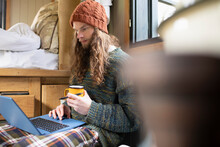 Young Man Using Laptop In Tiny Cabin Rental