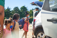 Mother And Daughters With Face Masks Loading Backpacks Into Car
