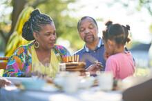 Grandparents And Granddaughter Enjoying Birthday Cake On Patio