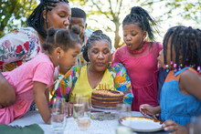 Multigenerational Family Blowing Out Birthday Candles On Patio Table