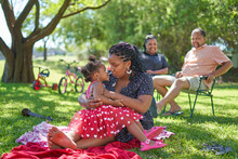 Affectionate Mother And Daughter Relaxing In Summer Park