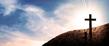 Man Kneeling In Front Of Cross Up Hill In Front Of Sunset And Panoramic Sky Landscape.  Person Wishing His God. Resurrection And Salvation Concept.