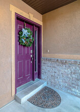 Vertical Home Facade With Purple Front Door Decorated With Wreath And Beside A Sidelight
