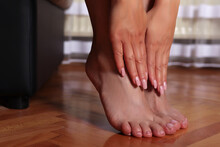 Female Feet And Hands With Nude Color Pedicure And Manicure On Parquet At Home. Skincare And Beauty Concept