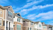 Pano Row Of Beautiful Houses On A Peaceful Neighborhood Set Against Cloudy Blue Sky