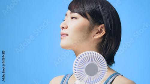 Photo ハンディファンを使う女性 ポータブル扇風機