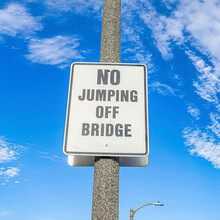 Square No Jumping Off Bridge Sign On Lamp Post Against Blue Sky And Puffy Clouds