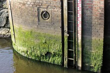 Water Level Dept Meter At Old Lock, With River Flowing Into The North Sea , Ballum Sluse, The Wadden Sea, South Jutland, Denmark