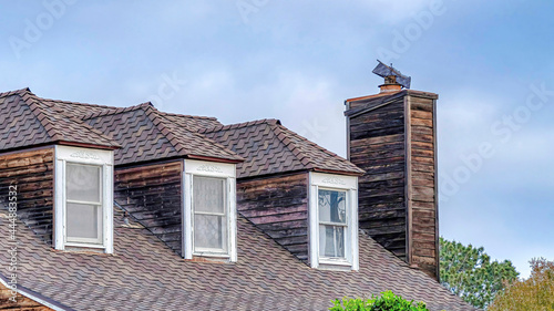 Foto Pano Dormer windows on gray roof of house with chimney in San Diego California