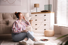 Young Woman Listening To Music With Turntable In Living Room