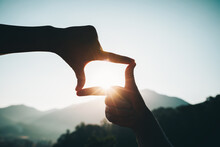 Silhouette Of Successful Woman Hands Making A Frame On Sunrise Mountain Top