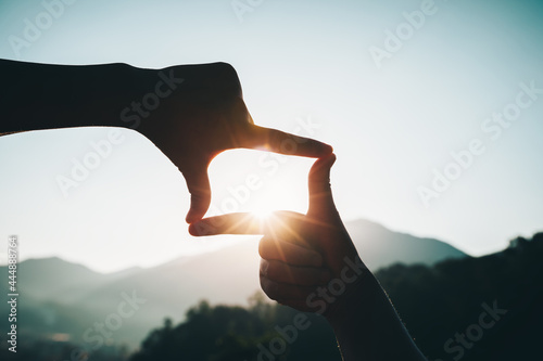 Платно Silhouette of successful woman hands making a frame on sunrise mountain top