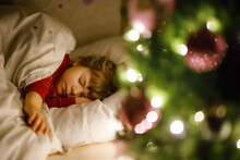 Little Cute Toddler Girl Sleeping Under Christmas Tree And Dreaming Of Santa At Home, Indoors. Traditional Christian Festival. Happy Kid Child Waiting For Gifts On Xmas. Cozy Soft Light