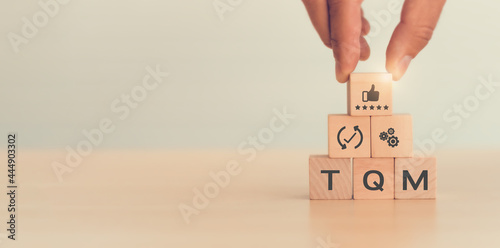 Fotomural Total quality management (TQM) concept, Text and icon on wooden cubes with light background and copy space
