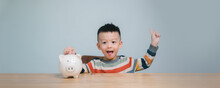 Little Asian Boy Saving Money In Piggy Bank, Learning About Saving Thinking About Something, Kid Save Money For Future Education. Money, Finances, Insurance And People Concept