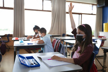 Caucasian Girl Wearing Face Mask Raising Her Hand While Sitting On Her Desk In The Class At School