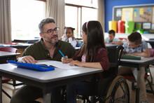 Caucasian Male Teacher Teaching Disabled Caucasian Girl Sitting On Wheelchair In Class At School