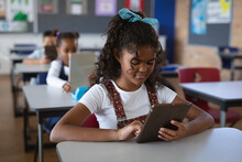 African American Girl Using Digital Tablet While Sitting On Her Desk In The Class At School