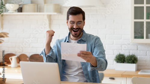 Photo Young 35s overjoyed man sit at table hold paper sheet, read good news in letter, celebrate success about job promotion, career advance looking very happy