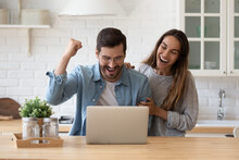 Family Standing In Domestic Kitchen Reading E-mail From Bank On Laptop Celebrate Loan Mortgage Approval, Happy Couple Of Lottery Victory, Great Commercial Offer, E-commerce Sale And Discount Concept