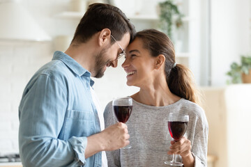 Loving young couple holding wine glasses touch foreheads relish romantic date harmonic relations celebrate life event, proposal or anniversary standing in kitchen at new own modern house. Love concept