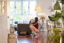 Serene Ballerina Sitting Near Sofa At Home