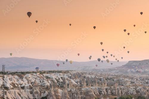 Fototapeta Hot air balloon flying over rock landscape at Cappadocia Turkey