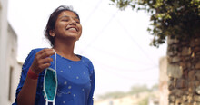 Young South Asian Girl Holding A Covid Mask In Her Hand And Smiling While Taking In The Fresh Air