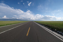 Empty Straight Asphalt Road Through Green Grass Plain. Heading To Wide Horizon And White Clouds Blue Sky. Wide Angle