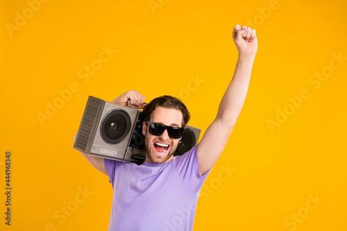 Fototapeta Photo of impressed lucky young guy dressed purple t-shirt dark glasses dancing b