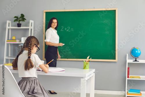 Fototapeta Primary or elementary school female teacher standing at chalkboard
