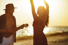 Couple In Love Playing Guitar And Dancing On The Beach