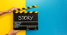 """The Hands Of The Camera Crew In The Film Industry Holding A Black Film Slate Or Clapperboard Write The Word """"story"""" With White Chalk. On A Yellow And Blue Background"""
