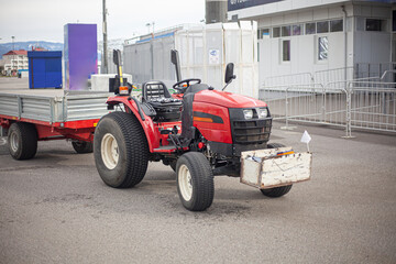 A small tractor transports a load. The machine is doing the job.