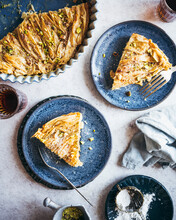 An Egyptian Phyllo Milk Pie (Um Ali) Plated On Blue Dishes, Served With Coffee And Garnishes Of Pistachio And Confectioner's Sugar