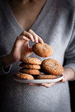 A Person In A Sweater Holding A Plate Of Cookies.