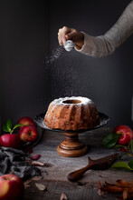 Bundt Cake On A Cake Stand Being Sprikled With Powdered Sugar