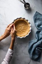 A Person Pressing Pastry Into A Dish