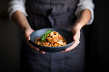 A Blue Bowl Of Pasta And Tomato Sauce Held By A Cook
