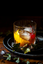 An Old Fashioned Cocktail With Ice, Lemon Zest And A Cocktail Cherry