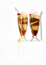 Two Root Beer Floats In Classic Milkshake Glasses Floating On A Glass Surface With Drips. White Background.